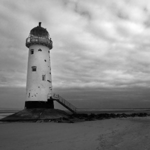 Black and white photo of a lighthouse on a sandy shore