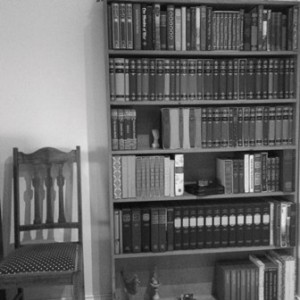 Black and white photo of bookcase and chair