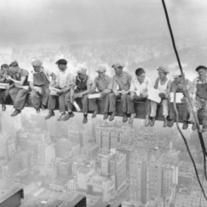 Black and white photo of workers taking a lunch break on a steel beam high above a city