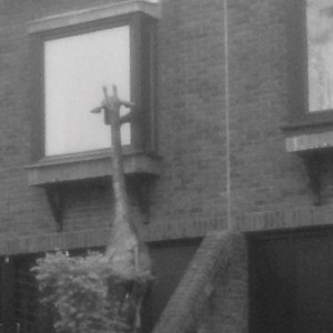 Upland Consulting - What Should Your Board Agenda Look Like. Black & white photo, giraffe sculpture looking in window.